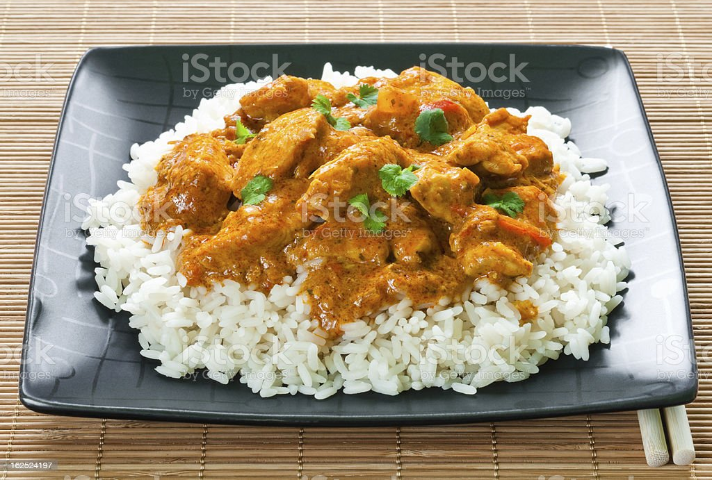 Chicken curry and rice on black plate on bamboo matting stock photo