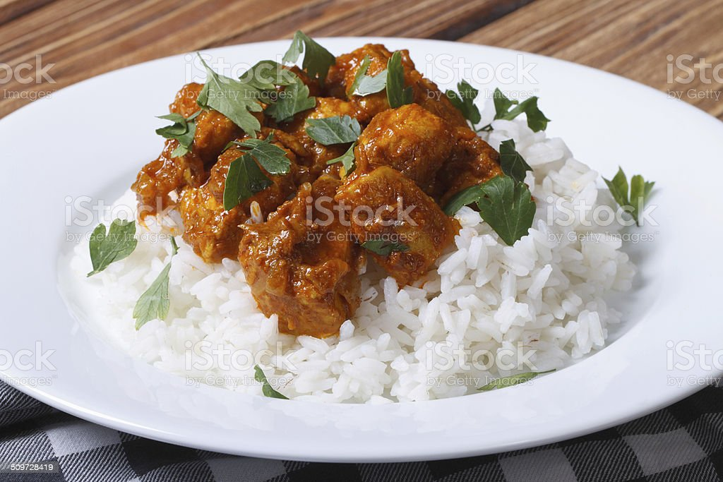 Chicken curry with rice and cilantro on white plate stock photo
