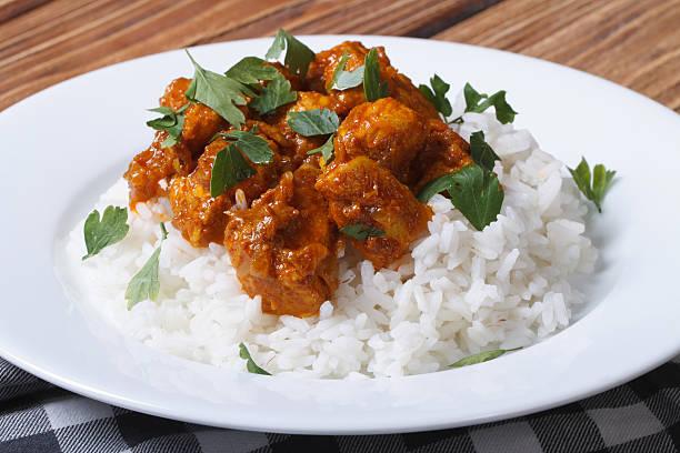 curry-huhn mit reis auf weißen teller und koriander - curry reis stock-fotos und bilder