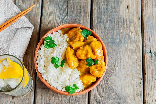 curry-huhn mit reis auf einem hölzernen oberfläche - curry reis stock-fotos und bilder