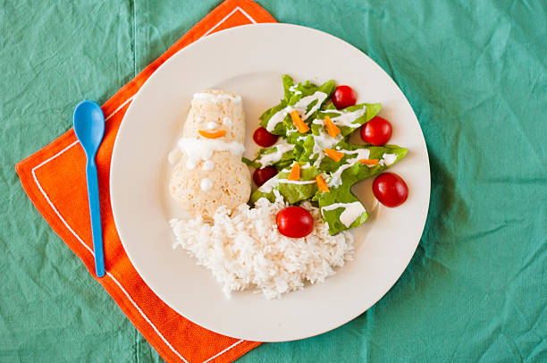 chicken cutlet snowman with rice and salad tree. - schnelles weihnachtsessen stock-fotos und bilder