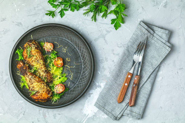 Chicken drumstick in a black ceramic plate with orange and rosemary stock photo