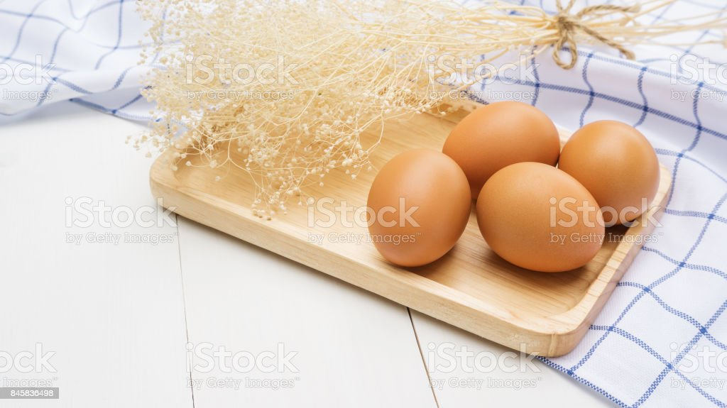 Chicken egg on a wooden plate. stock photo