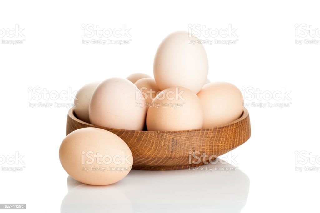 chicken eggs in a wooden plate isolated on white background stock photo