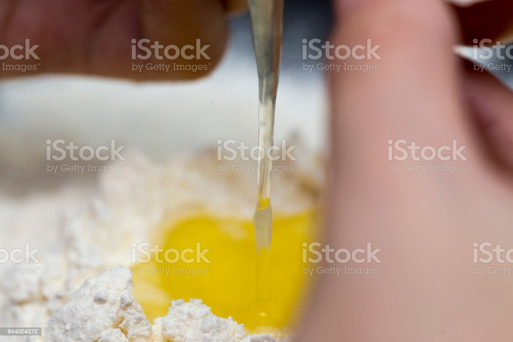 Chicken eggs in white plate and slide around her meal with a broken egg. The process of making of the test. Eggs, flour, a plate on a black background. stock photo