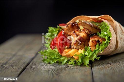 Chicken fajita wrap sandwich. Sandwich with fajita chicken. Roll with chicken meat fresh tomatoes and cucumbers, lettuce wrapped in bread pita