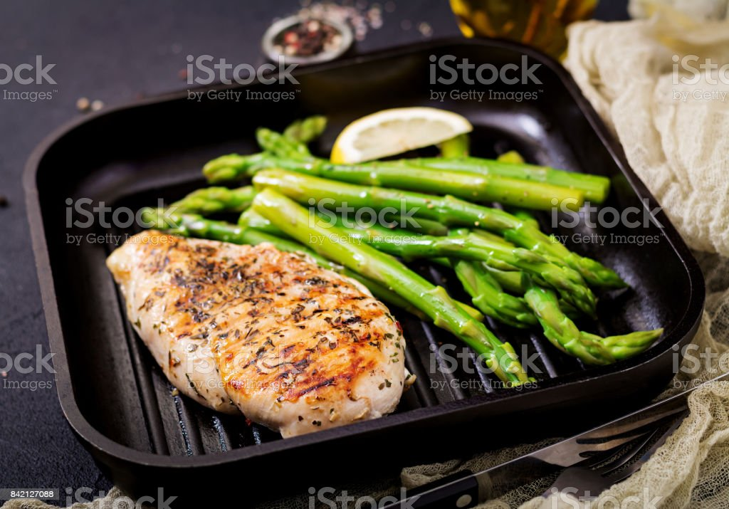 Chicken fillet cooked on a grill and garnish of asparagus stock photo