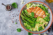 istock Chicken fillet cooked on a grill with a garnish of asparagus and grilled avokado. Dietary menu. Healthy food. Flat lay. Top view 939951530