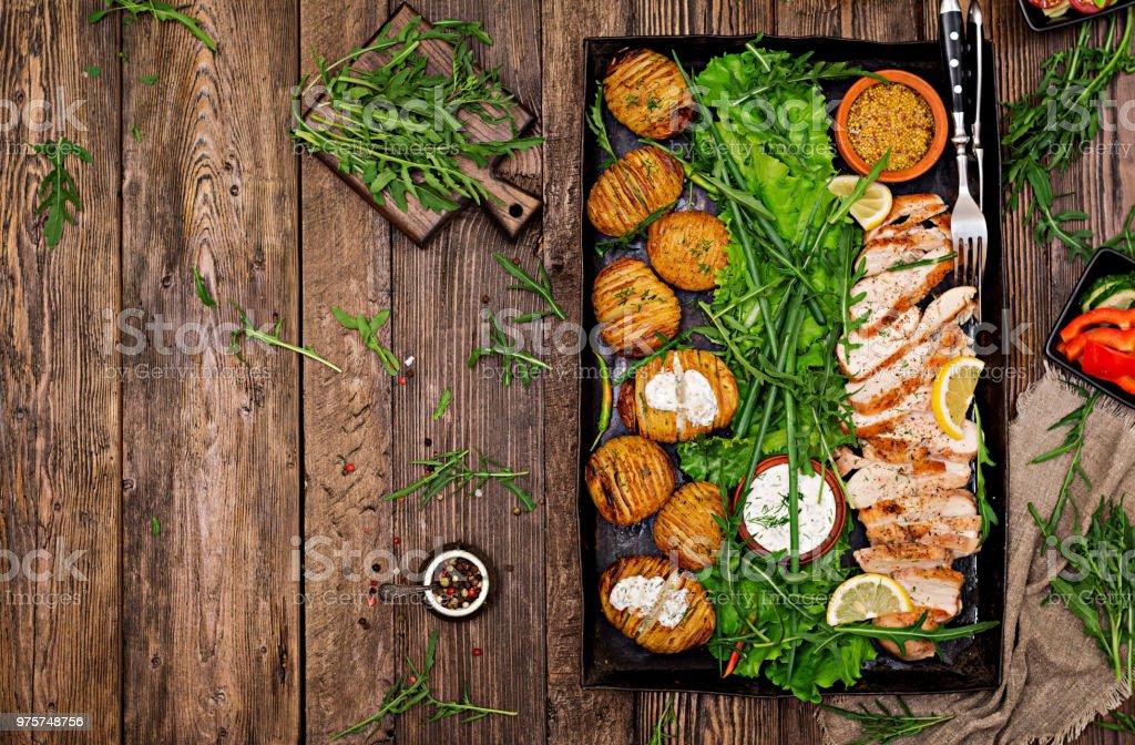 Hähnchenfilet auf einen Grill mit einer Garnierung von gebackenen Kartoffeln gekocht. Diätetische Mahlzeiten. Gesunde Ernährung. Ansicht von oben. Flach zu legen - Lizenzfrei Asiatisch Stock-Foto