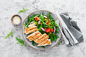Chicken fillet salad with fresh vegetables and arugula. Fresh vegetable salad of arugula, tomatoes, onion and grilled chicken breast.