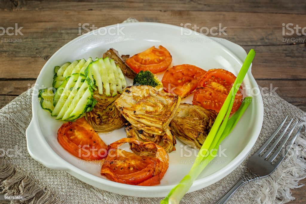 chicken fillet with fresh cucumber, artichoke and pepper on white ceramic frying pan royalty-free stock photo