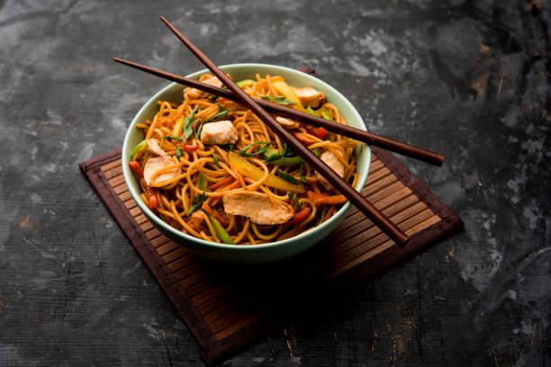 kip hakka/schezwan noedels geserveerd in een kom met eetstokjes. selectieve focus - aziatische noedels stockfoto's en -beelden