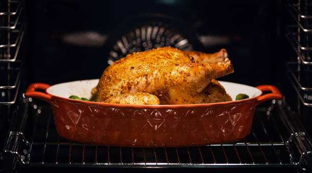 Chicken in an oven. Closeup side view of a chicken in a clay pot roasting in an oven. It's almost  done with golden crispy skin and some green vegetables. oven stock pictures, royalty-free photos & images
