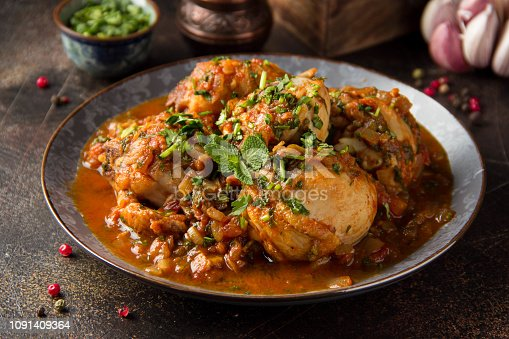 Chicken in tomato sauce with herbs and onions, cilantro parsley mint, traditional Oriental dish chakhokhbili, delicious homemade food. On dark background