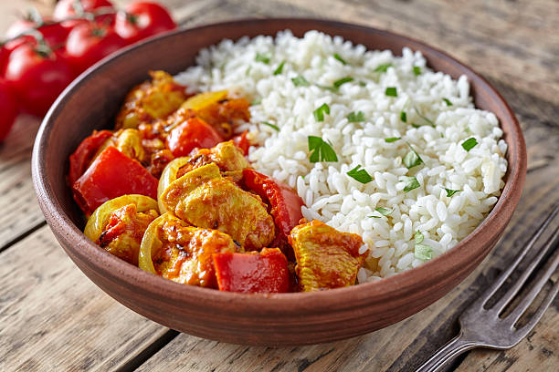 Chicken jalfrezi healthy traditional Indian curry spicy fried meat with Chicken jalfrezi healthy traditional Indian curry spicy fried meat with vegetables and basmati rice food in clay plate on vintage table background balti dish stock pictures, royalty-free photos & images