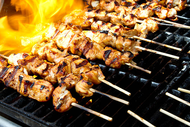 Chicken kabobs on a flaming grill stock photo
