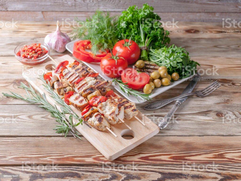 Chicken Kebab. Frisches Gemüse und Kräuter. Rote Tomaten, rote Paprika, Petersilie, Dill, Rucola, Knoblauch, Rosmarin. - Lizenzfrei Bratengericht Stock-Foto