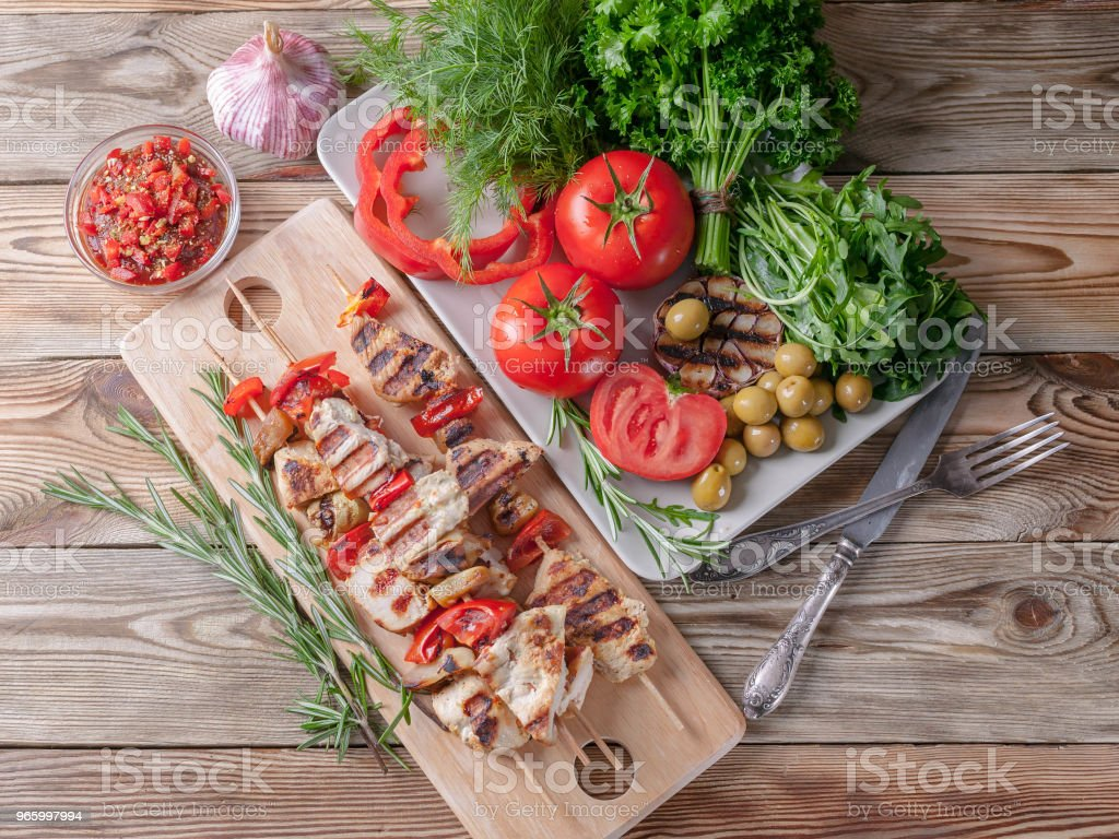 Kycklingkebab. Färska grönsaker och örter. Röda tomater, röd paprika, persilja, dill, ruccola, vitlök, rosmarin. Ovanifrån - Royaltyfri Aperitif - Måltid Bildbanksbilder