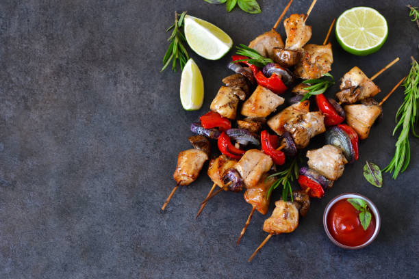 chicken kebab on skewers with mushrooms and peppers and barbecue sauce on a black background. food for a picnic - kebab marinade stock-fotos und bilder