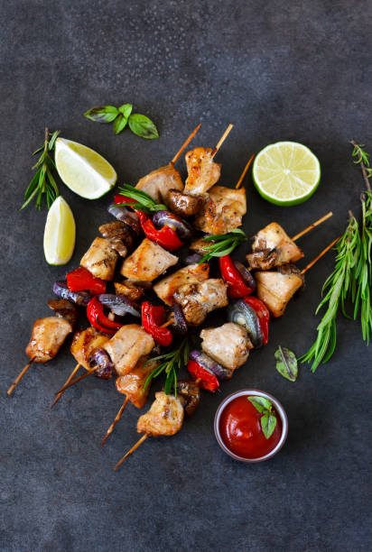 chicken kebab on skewers with mushrooms and peppers and barbecue sauce on a black background. food for a picnic - spieße grillen stock-fotos und bilder