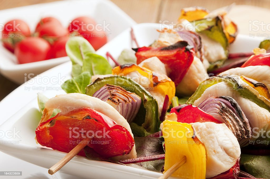 Chicken kebab skewer with peppers and onion on white plate royalty-free stock photo
