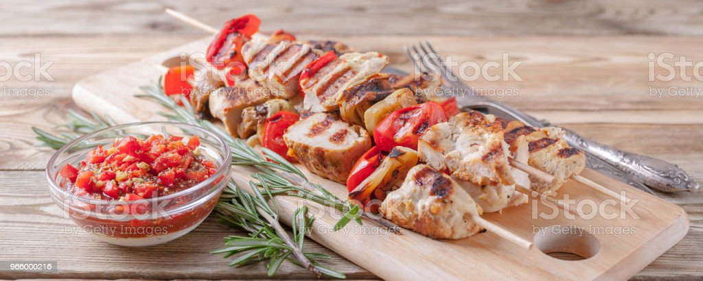 Chicken kebab with grilled vegetables and spicy tomato sauce on a cutting board on a wooden table. Close up. Banner - Royalty-free Almoço Foto de stock