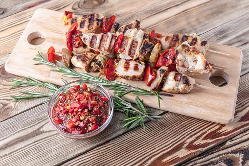 Kip Kebab Met Gegrilde Groenten En Pittige Tomatensaus Op Een Snijplank Op Een Houten Tafel Closeup Stockfoto en meer beelden van Avondmaaltijd
