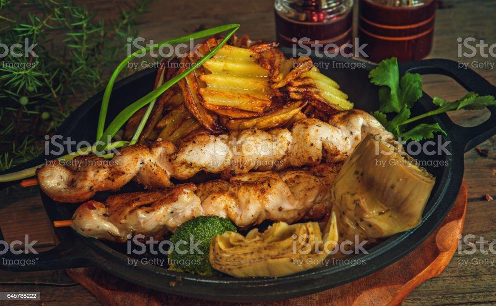 chicken kebabs on wooden skewers with vegetables rustic stock photo