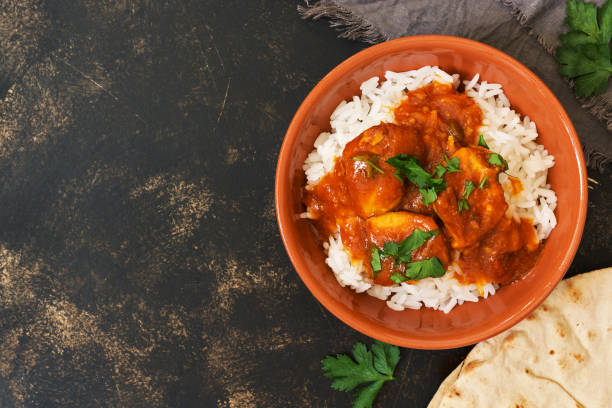 Chicken korma with a spicy sauce over white rice.Traditional Indian dish on a rustic background. Top view, copy space. stock photo