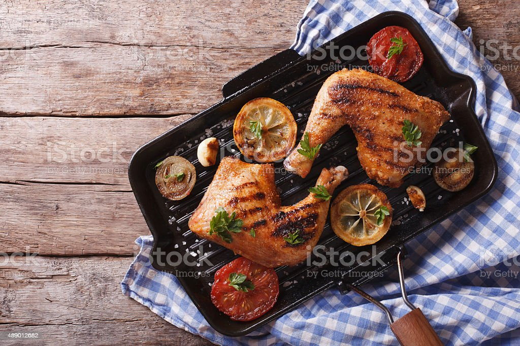 chicken leg and vegetables on grill pan. horizontal top view stock photo