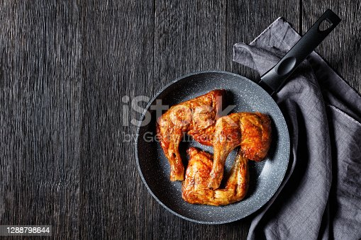 Chicken leg quarters served on a frying pan on a wooden background, top view, close-up