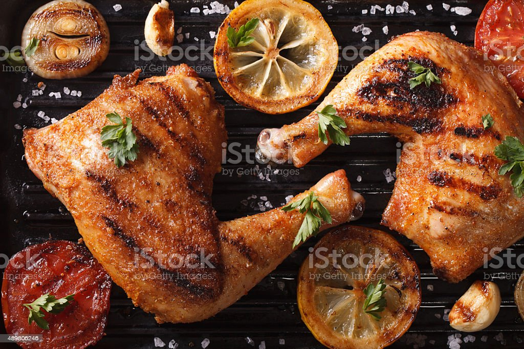 chicken legs and vegetables on grill macro. Top view horizontal stock photo