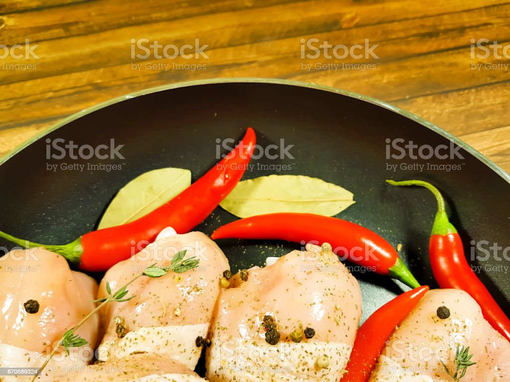 chicken legs raw, frying pan, red chili pepper stock photo