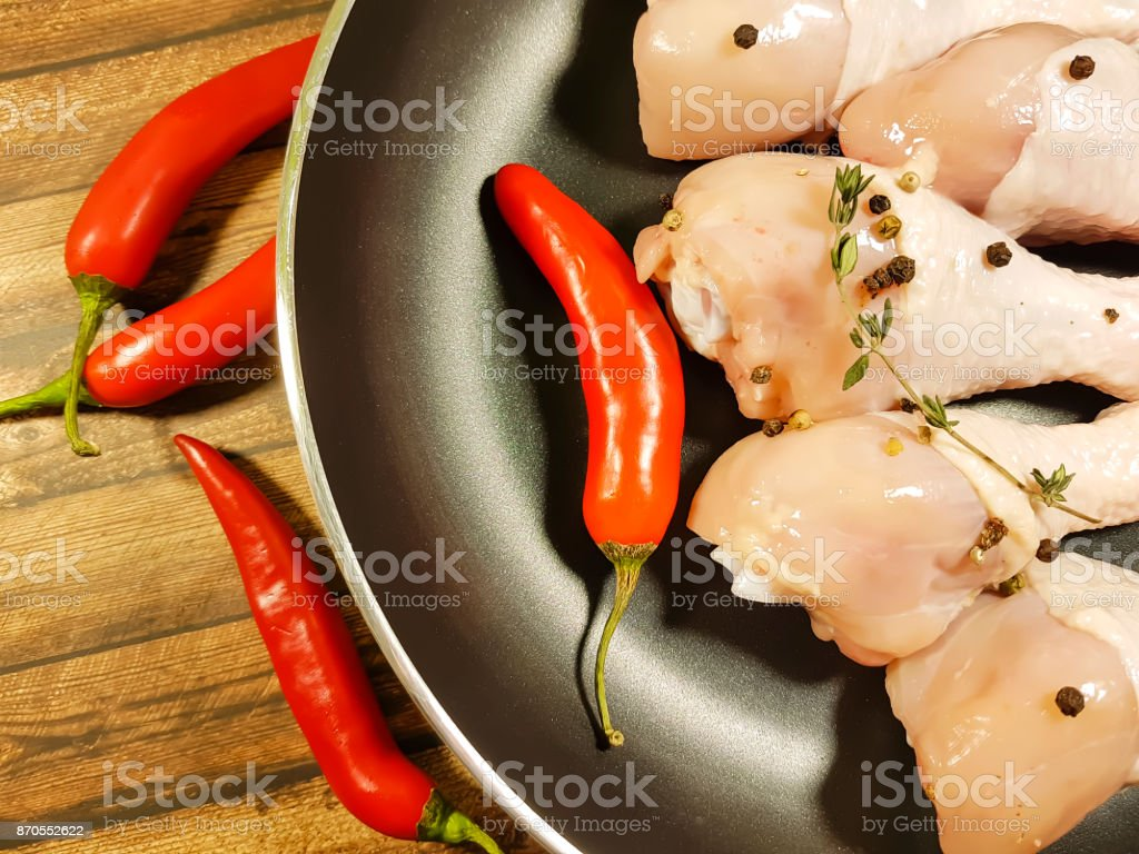 chicken legs raw frying pan red chili peppers stock photo