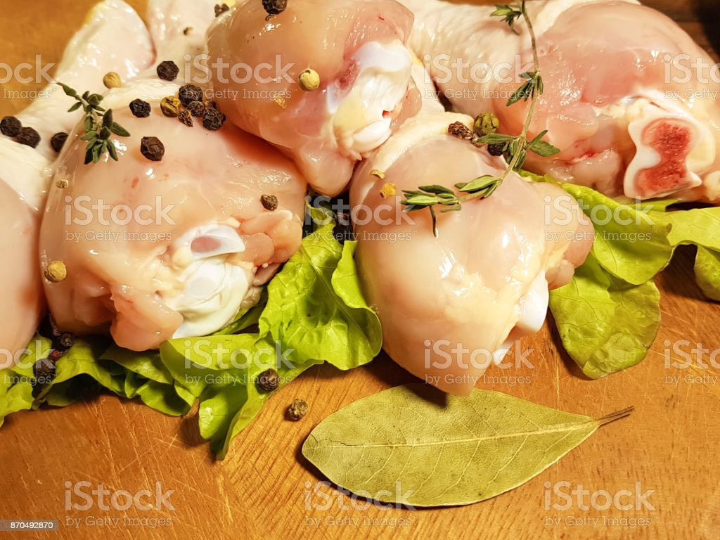 chicken legs raw, preparation, cooking, bay leaf, spice, black pepper stock photo