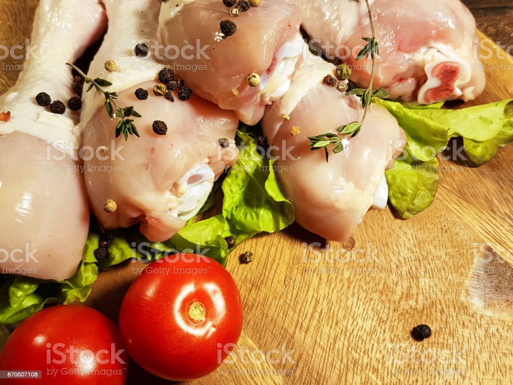 chicken legs raw, preparation, cooking, bay leaf, spice, black pepper, tomato stock photo