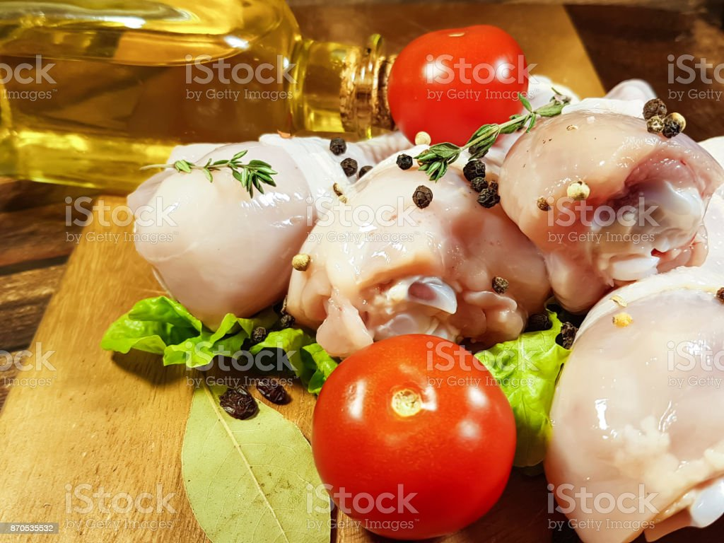 chicken legs raw, preparation, cooking, bay leaf, spice, black pepper, tomato, olive oil stock photo