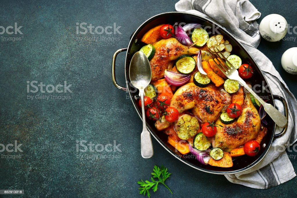 Chicken legs roasted with vegetables in a skillet pan stock photo