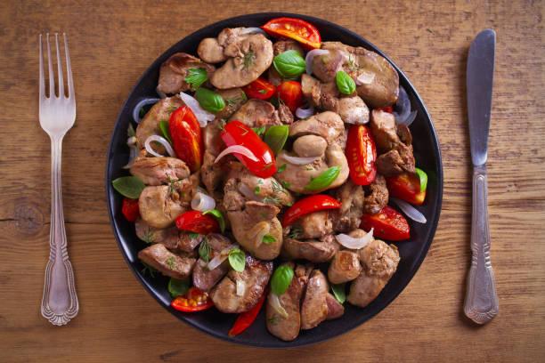 hühnerleber mit tomaten, zwiebeln und basilikum auf schwarzem teller, holztisch - innereien stock-fotos und bilder