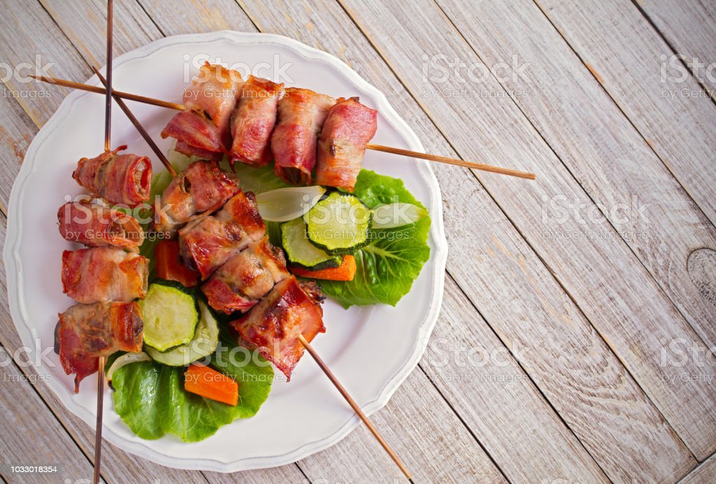 Chicken liver wrapped with bacon on skewers. Grilled liver kebabs stock photo