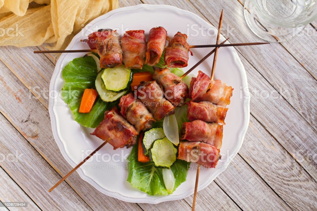 Chicken liver wrapped with bacon on skewers. Grilled liver kebabs with vegetables stock photo