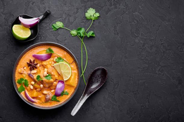 um frango massaman curry em tigela preta ao fundo de ardósia escura. massaman curry é prato da cozinha tailandesa com carne de frango, batata, cebola e muitos temperos. comida tailandesa. copiar espaço. vista superior - caril - fotografias e filmes do acervo