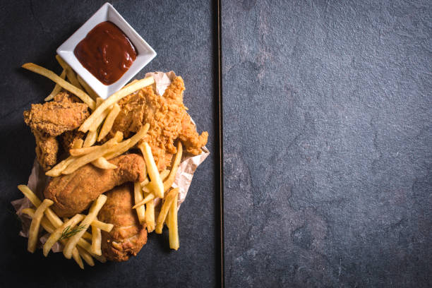 Chicken meat and french fries Fried chicken meat and French fries from above,blank space on the right side fried chicken stock pictures, royalty-free photos & images