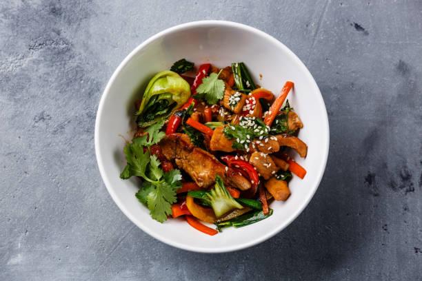 hühnerfleisch mit gemüse in die schüssel rühren braten im wok - paprika hähnchen stock-fotos und bilder