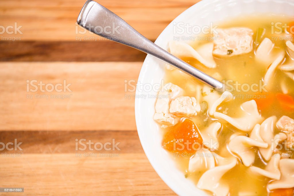 Chicken noodle soup in bowl. Spoon, crackers. Copyspace. stock photo