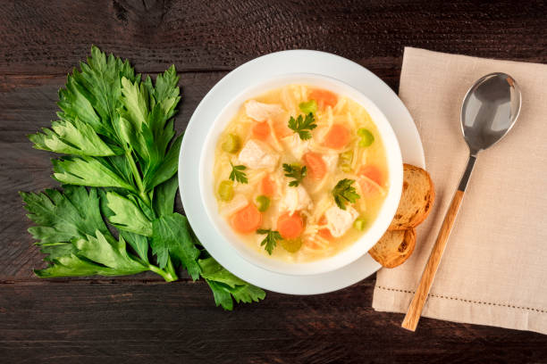Chicken noodle soup, shot from the top on a dark rustic wooden background stock photo