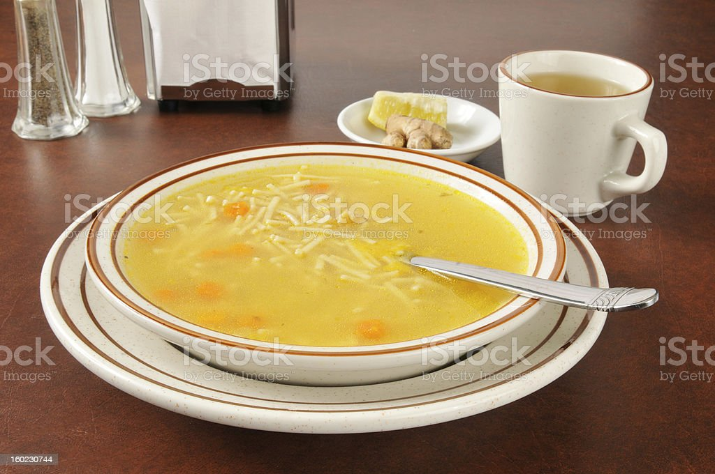 Chicken noodle soup with tea, lemon and ginger stock photo