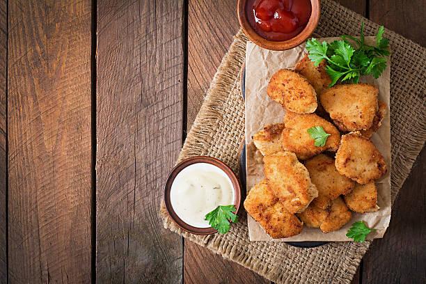 Chicken-nuggets und Soße auf einem hölzernen Hintergrund – Foto