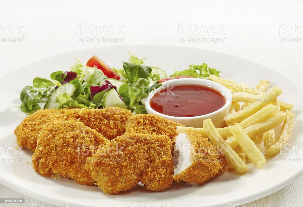 Chicken nuggets chips salad and red sauce on a white plate stock photo
