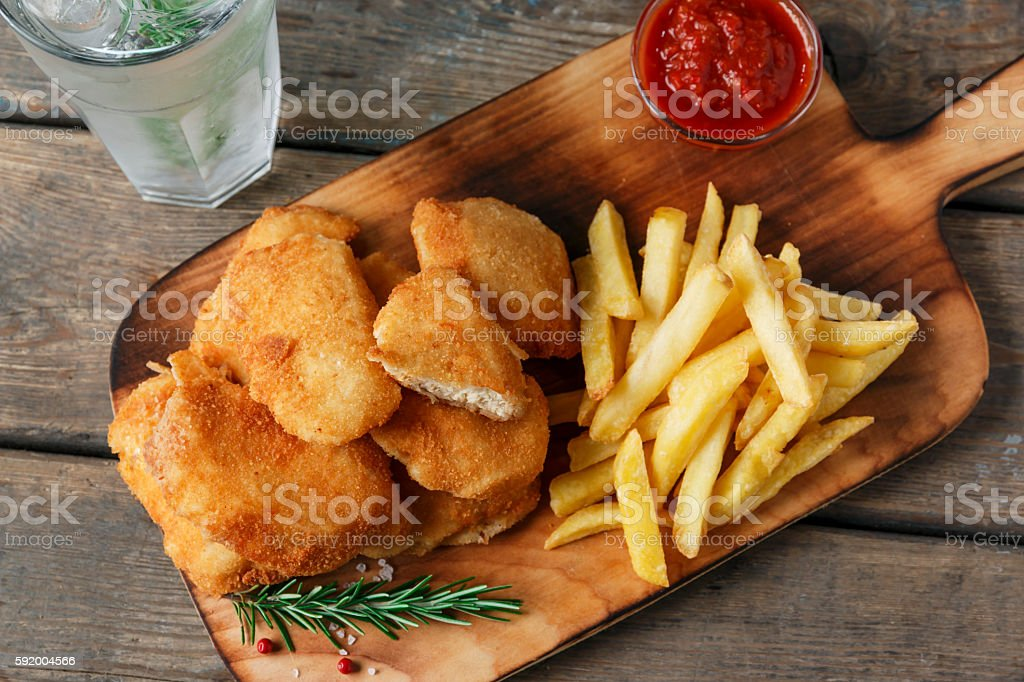 chicken nuggets french fries on the board with red sauce stock photo
